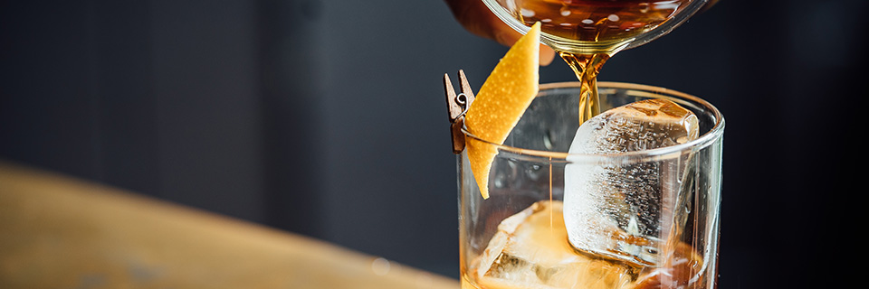 Pouring tea over ice in a glass with a piece of lemon rind clothespinned to the rim