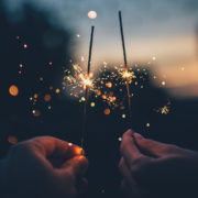 Two hands holding fizzing sparklers in the dark