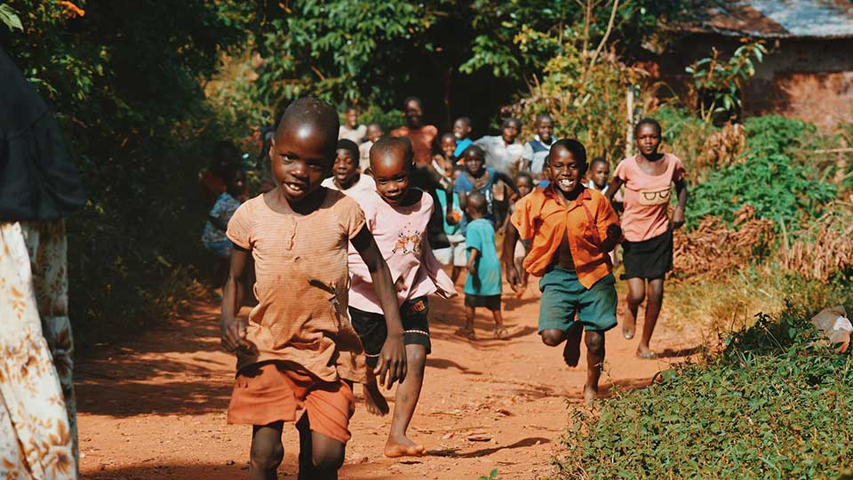 Kids running in Africa on a sand road by Seth Doyle at Unsplash
